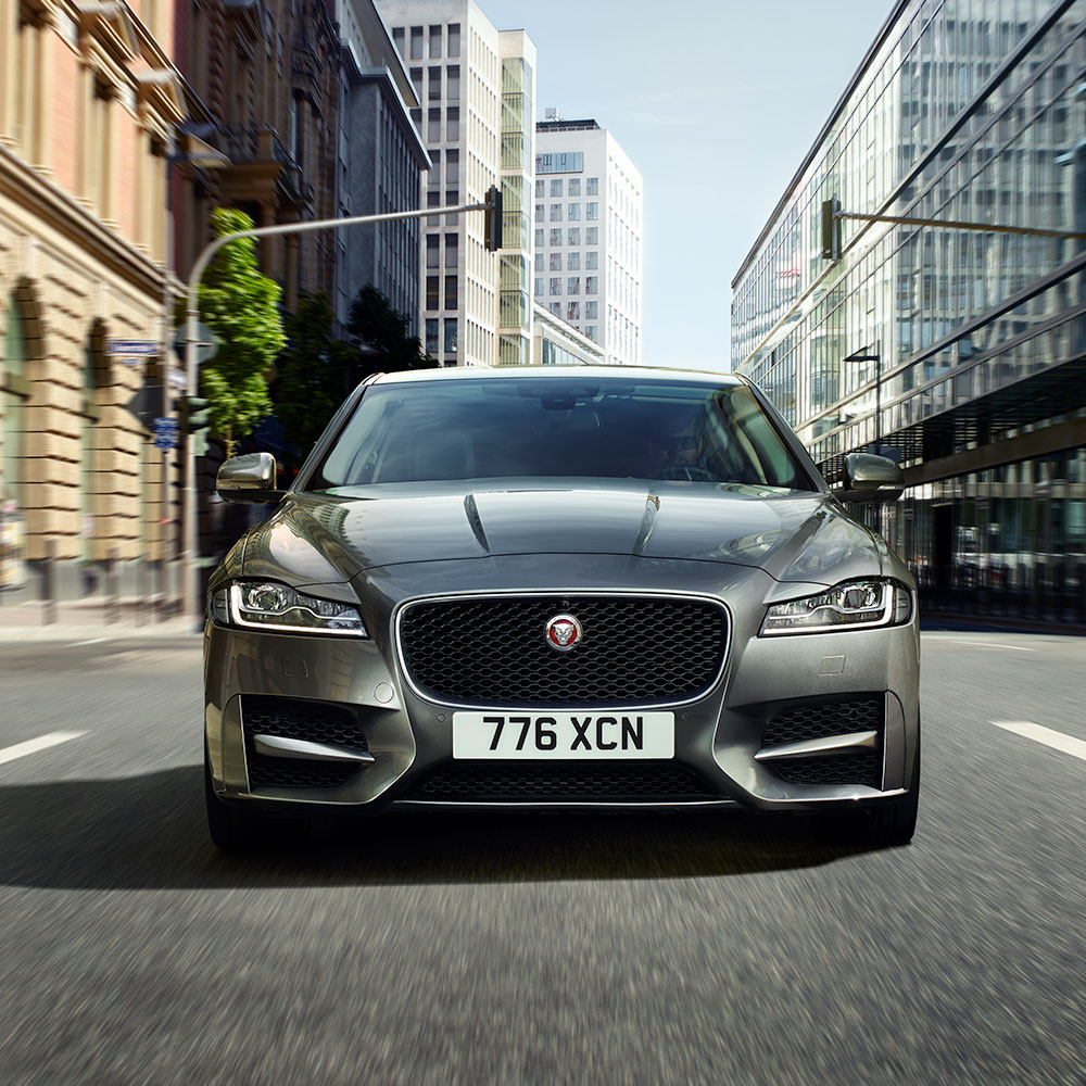 Jaguar XF in the middle of the road of a metropolis.