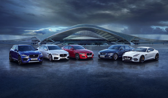 5 JAGUAR CARS ARRANGED IN FRONT OF A DARK CITYSCAPE.