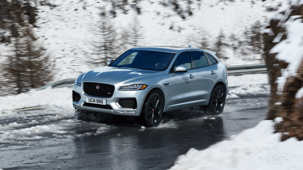 Jaguar F-PACE in grey driving in the snow.