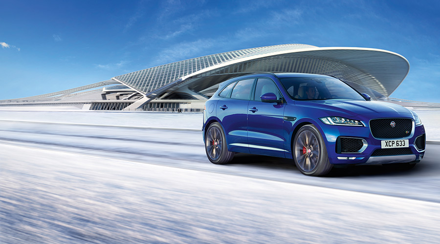 Blue Jaguar F-TYPE driving on a road surrounded by snow and a large modern building.