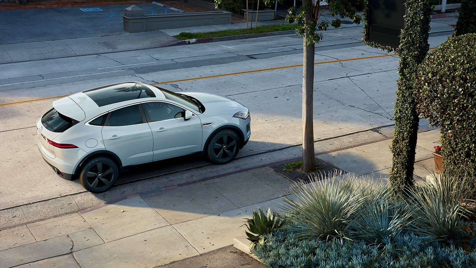E-PACE R-DYNAMIC SE IN YULONG WHITE WITH OPTIONAL FEATURES FITTED PARKED IN A CITY BY TREES.