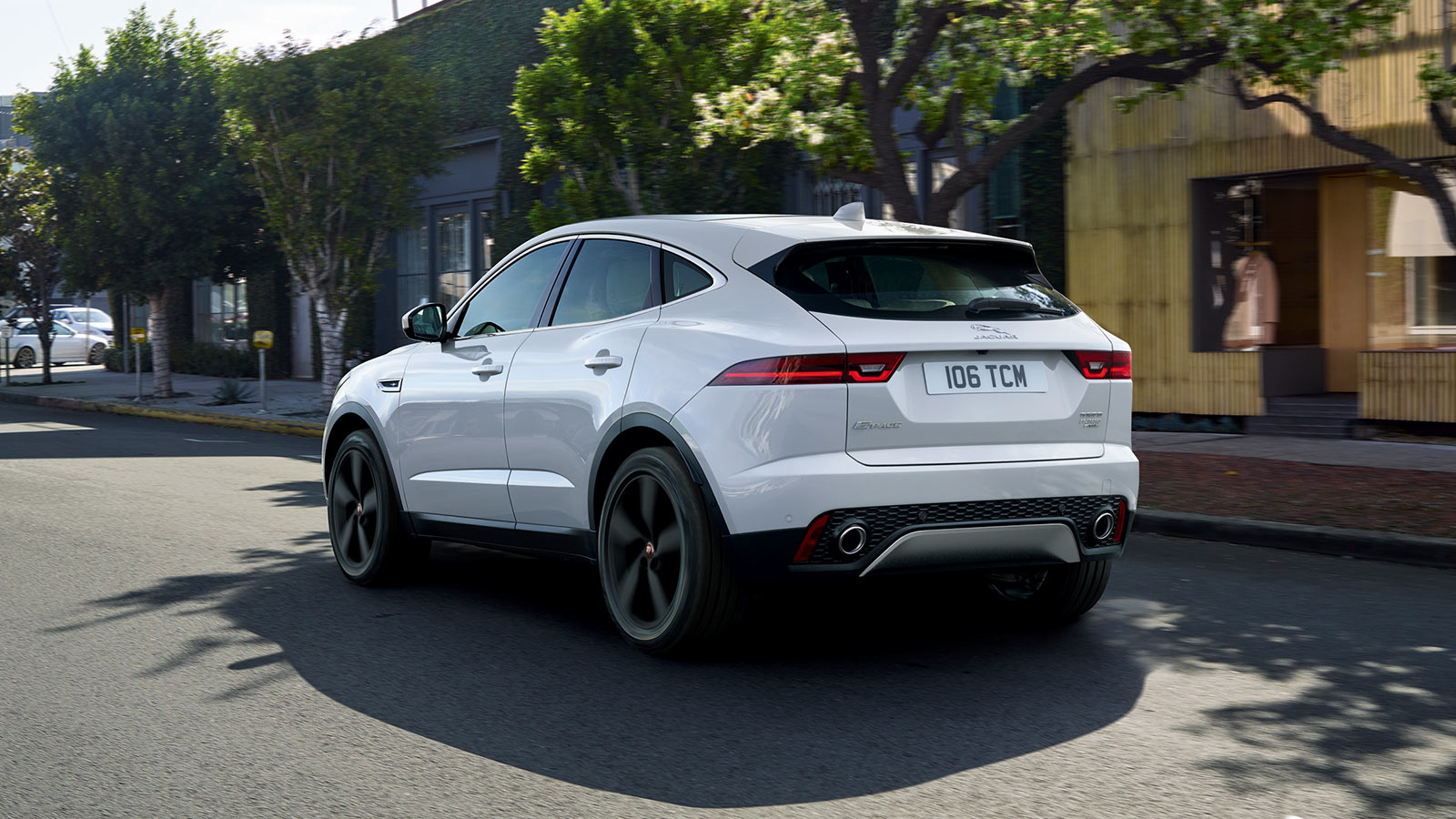 E-PACE S IN BORASCO GREY WITH OPTIONAL FEATURES FITTED DRIVING PAST SHOPS IN A CITY.