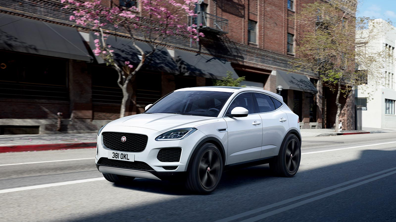 E-PACE S IN BORASCO GREY WITH OPTIONAL FEATURES FITTED DRIVING DOWN CITY STREET.
