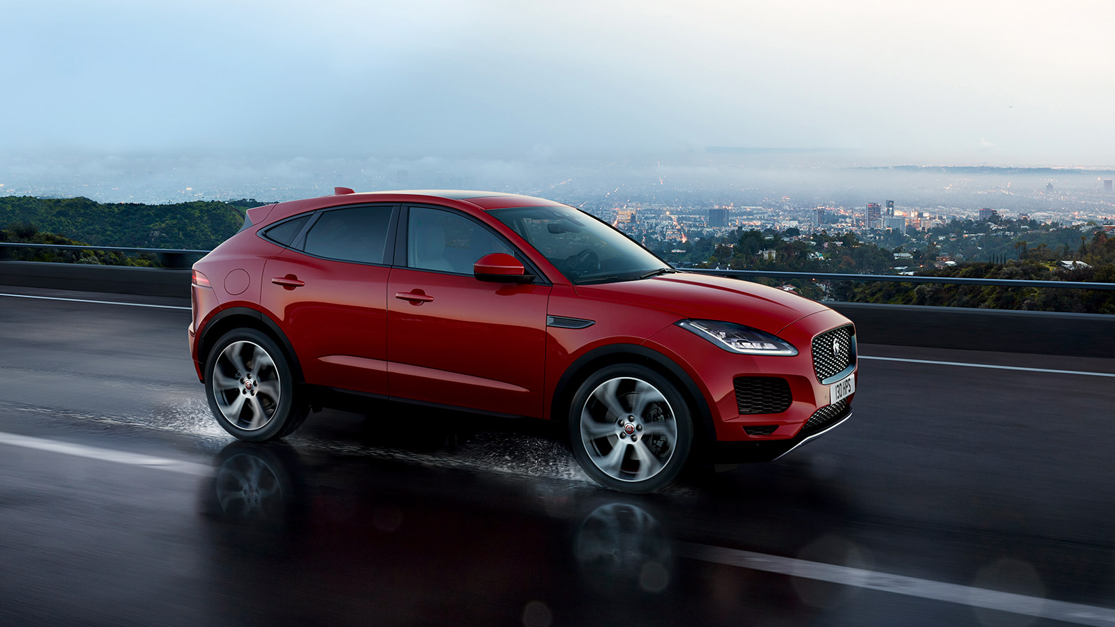 Red jaguar E-Pace driving on wet road with a cityscape in the distant.
