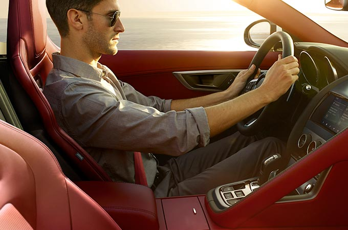 Interior view of man driving F-TYPE with standard occupant safety features