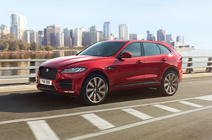 Red jaguar F-PACE driven on road.
