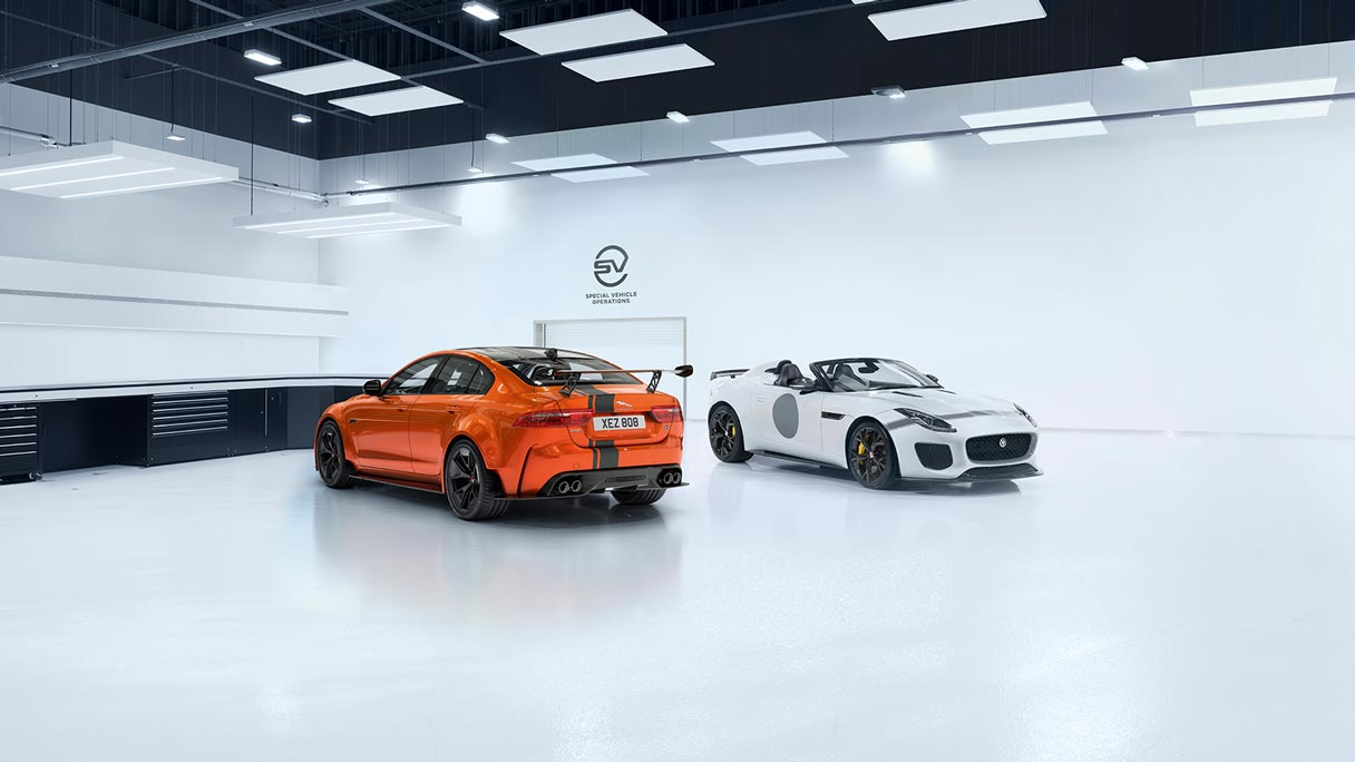 Jaguar XE SV Project 8 in orange from behind, next to a Jaguar F-TYPE SVR inside the Special Vehicle Operations Centre